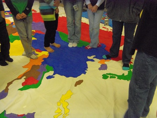 KidZ at Heart NextGen and FamMin ministries kids standing on a world map